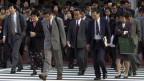 Eine Masse von japanischen Büroarbeitern, die Männer in Anzug, Krawatte, die Frauen in Kleidern oder Deux-Pièce, überquert eine Strasse.