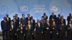Teilnehmer der Klimakonferenz posieren mit emporgehobenen Daumen für ein Gruppenfoto.