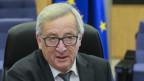 EU-Kommissionspräsident auf einem Bürostuhl, weisse Haare, schwarze Brille, er schaut besorgt.