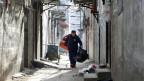 Ein Wanderarbeiter verlässt mit seinen Habseligkeiten sein Zuhause, nachdem in einem Wohnblock in Peking bei einem Brand 19 Menschen ums Leben kamen. Nun werden zahlreiche Häuser zwangsgeräumt.