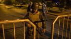 Einer vom Militär bewacht die Strasse mit einer Waffe in der Hand.