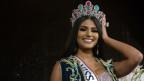 Die Miss Venezuela 2017 Sthefany Gutierrez - lange schwarze Haare, stark geschminkt, eine Krone auf und eine Schärpe um den Torso, sie lacht breit und hält sich die linke Hand an den Kopf.