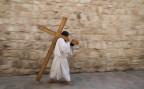 Ein christlicher Pilger trägt ein Kreuz durch die Via Dolorosa in Jerusalem.