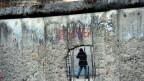 Eine Spaziergängerin geht in Berlin an Resten der Berliner Mauer in der Gedenkstätte «Topographie des Terrors» vorbei.