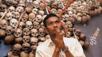 Ein junger Kambodschaner betet vor einem Bild mit Totenköpfen im ehemaligen Gefängnis der Roten Khmer in Phnom Penh, Tuol Sleng.