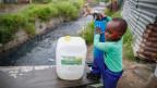 Ein Junge holt Wasser am Brunnen in Kapstadt.