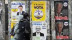 Ein Paar spaziert vorbei an italienischen Wahlplakaten.