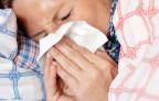 Eine Frau liegt mit Grippesymptomen im Bett.