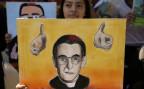 Eine Frau in San Salvador hält ein selbstgezeichnetes Portrait hoch des ermordeten Erzbischofs Oscar Romero.