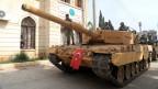 Ein Panzer mit einer türkischen Flagge fährt duch das Stadtzentrum des nordsyrischen Afrin