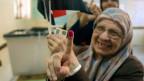 Magdah Ahmed, 78, zeigt ihren mit Tinte markierten Finger, nachdem sie am ersten Tag der Präsidentschaftswahl in einem Wahllokal in Kairo ihre Stimme abgegeben hat.