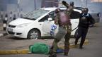 Ein kenianischer Polizist geht einen am Boden liegenden Demonstranten brutal an.