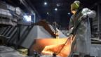 Ein Arbeiter des deutschen Stahlherstellers Salzgitter AG vor einem Ofen.