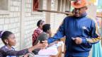 Der Präsident von Burundi, Pierre Nkurunziza, wird von einer Wahlbeamtin registriert.