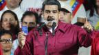 Venezuelas Präsident Nicolas Maduro tritt nach seiner Wiederwahl vor Anhängern auf - mit einer Taschenausgabe der venezolanischen Verfassung in der Hand.