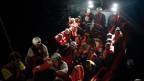 Flüchtlinge werden auf das italienische Rettungsschiff Aquarius begleitet.