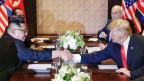 Donald Trump und Kim Jong Un reichen sich über den Verhandlungstisch die Hand.