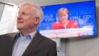 Horst Seehofer, CSU-Vorsitzender, geht an einem Fernseher vorbei, auf dem die Pressekonferenz von Bundeskanzlerin Angela Merkel (CDU) übertragen wird.