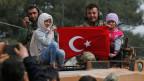 Türkische Soldaten in der Stadt Afrin und syrische Kinder, die die türkische Fahne hochheben.