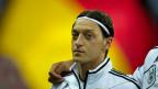 Der deutsche Fussballer Mesut Özil vor einer Deutschlandfahne. Archivaufnahme von 2012.