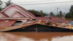 Ein Dorfbewohner rettet sich vor dem Hochwasser aufs Dach. Mehr als 6'600 Menschen sind obdachlos machten.