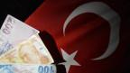 Türkische Lira vor einer türkischen Fahne.