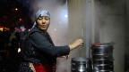 Eine Uigurin beim Kochen.