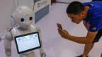 Ein Besucher fotografiert einen Roboter während der World Robot Konferenz 2018 in Peking, China, am 15. August 2018.