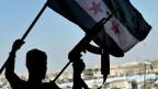 Ein bewaffneter Mann hält die syrische Fahne in die Höhe.