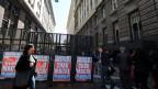 Menschen gehen an Plakaten vorbei, auf denen steht «Schluss mit Lügen -  Auf Wiedersehen, Macri» vor dem Wirtschaftsministerium in Buenos Aires.