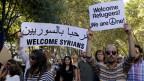 """Demonstranten in Lissabon halten Plakate in die Höhe auf denen """"Syrian Refugees welcome"""" steht."""