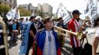 Ein Jugendlicher bläst an einem Protestmarsch eine Trompete.