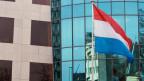 Die luxemburgische Nationalflagge wird vor dem Hauptsitz der Bank von Luxemburg im Zentrum von Luxemburg.