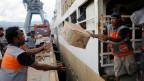Hilfspakete für Erdbeben- und Tusnami-Opfer werden von einem Schiff in Palu entladen.