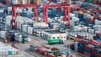 Lastwagen zwischen gestapelten Frachtcontainern im Yangshan-Hafen in Shanghai.