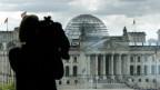 Blick auf den Bundestag. Kameramensch im Vordergrund.