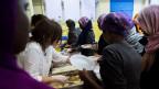 Freiwillige Helferinnen verteilen ein Essen an Flüchtlinge.