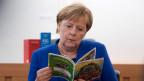 Bundeskanzlerin Angela Merkel mit der Broschüre «Fit für den Rechtsstaat - fit für Hessen».