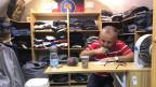 Khaled Essaheb sitzt in seinem winzigen Kleiderladen und wartet auf Kundschaft.