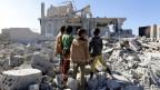 Kinder in Jemen stehen vor den Trümmern einiger Häuser.