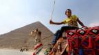 Ein Junge wartet auf seinem Kamel auf Touristen in der Nähe der Khufu-Pyramide.