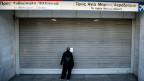 Streik in Griechenland: Eine Frau steht vor einem geschlossenen U-Bahn-Tor.