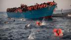 Migranten springen von einem überfüllten Holzboot ins Wasser vor Libyen.