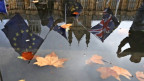 Das britische Parlament spiegelt sich in einer Pfütze - EU-Flaggen und GB-Flaggen wehen davor.