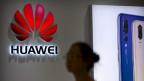 Eine Frau steht vor dem Logo von Huawei.