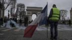 Mann steht mit Frankreich-Flagge vor dem Triumph-Bogen in Paris.