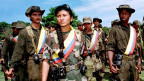 Eine weibliche Guerilla steht mit ihren Mitstreiterinnen während einer Trainingseinheit im Dschungel.