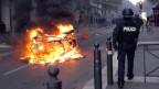 Ein Polizist steht neben einem brennenden Auto.