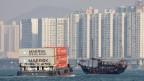 Ein Containerschiff und eine traditionelle Barkasse vor Hongkong.