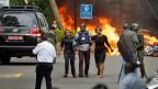 Ein Sicherheitsmann bringt nach dem Attentat auf einen Hotelkomplex in der kenianischen Hauptstadt Nairobi Zivilistinnen in Sicherheit.